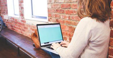 Chica rubia de pelo rizado estudiando online con su ordenador portátil para mejorar su inglés profesional.